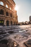 Coliseum Cobblestone Ice and Snow. A sun flare in a sunny Roman afternoon in Rome Italy.  The Roman cobblestone is paved with ice and snow, featuring a sun flare Royalty Free Stock Photos
