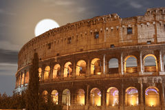 Coliseum Night Moon (Colosseo - Rome - Italy). Coliseum - Night (Colosseo - Rome - Italy) - Lights shadows on the ancient monument of the Roman Empire Stock Photo