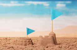 Coliseum and sand castle, flags on background of coast. royalty free stock images