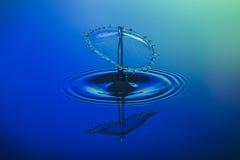 Colisión del descenso del agua en fondo azul Imagen de archivo libre de regalías