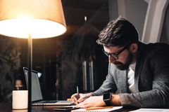 Collègue barbu travaillant à côté de la table en bois avec l'ordinateur portable L'homme créatif d'affaires font le nouveau démar Photos stock