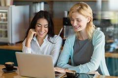 Collègue d'affaires à l'aide de l'ordinateur portable dans le café Photos stock