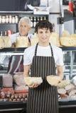 Collègue de Holding Cheese While de vendeur travaillant au compteur Image stock
