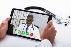 Collègue masculin de docteur Video Conferencing With sur la Tablette de Digital images stock