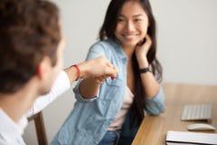 Collègue masculin se cognant de sourire de poing asiatique de jeune femme au travail Image stock