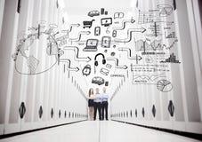 Collègues à un centre de traitement des données se tenant devant un dessin Image libre de droits