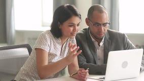 Collègues africains et asiatiques parlant regardant l'ordinateur portable dans le bureau banque de vidéos