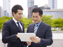 Collègues asiatiques employant l'ipad Photos stock