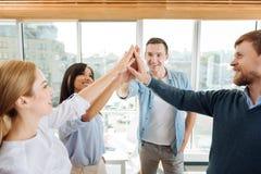 Collègues avec plaisir touchant leurs mains Image stock