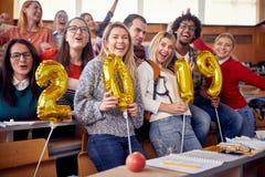 Collègues ayant l'amusement à la célébration de nouvelle année sur l'université photographie stock libre de droits