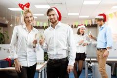 Collègues célébrant la fête de Noël dans le sourire potable de champagne de bureau Photos stock