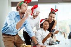 Collègues célébrant la fête de Noël dans le sourire potable de champagne de bureau Photos libres de droits