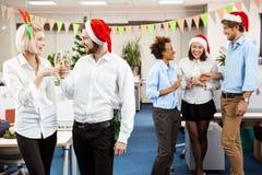 Collègues célébrant la fête de Noël dans le sourire potable de champagne de bureau Image stock