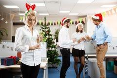 Collègues célébrant la fête de Noël dans le sourire potable de champagne de bureau Photographie stock
