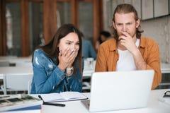 Collègues ce amazedly regard sur l'ordinateur portable tout en travaillant ensemble dans le bureau Jeunes étudiants s'asseyant à  Photographie stock