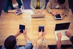 Collègues créatifs avec l'ordinateur portable et le bureau numérique de comprimé Photos stock