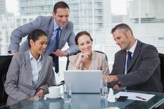 Collègues décontractés analysant des documents sur leur ordinateur portable Image stock