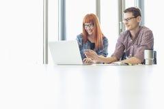 Collègues d'affaires à l'aide de l'ordinateur portable au bureau dans le bureau créatif Photo libre de droits