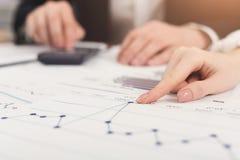 Collègues d'affaires à l'aide de la calculatrice et travaillant avec des documents Image stock