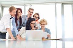 Collègues d'affaires avec l'ordinateur portable analysant le document dans le bureau créatif Photographie stock libre de droits