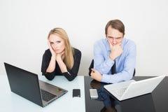 collègues d'affaires avec l'ordinateur portable et le comprimé numérique lors de la réunion au bureau triste Image libre de droits