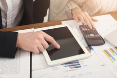 Collègues d'affaires comptant sur la calculatrice et à l'aide du comprimé Images libres de droits