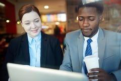 Collègues d'affaires dans le café utilisant l'ordinateur portable Photos libres de droits