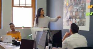 Collègues d'affaires discutant au-dessus des photographies lors de la réunion 4k banque de vidéos