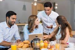 Collègues d'affaires discutant au-dessus du comprimé numérique tout en prenant le petit déjeuner Images libres de droits