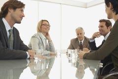 Collègues d'affaires discutant dans la salle de conférence Image stock