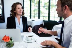Collègues d'affaires discutant et prenant des notes tout en ayant une réunion Photos stock