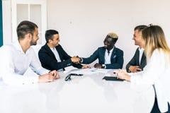 Collègues d'affaires s'asseyant à une table au cours d'une réunion avec deux cadres masculins se serrant la main Team le travail photo stock