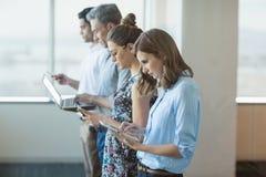 Collègues d'affaires se tenant dans une rangée utilisant le téléphone portable, le comprimé numérique et l'ordinateur portable Images stock