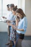 Collègues d'affaires se tenant dans une rangée utilisant le téléphone portable, le comprimé numérique et l'ordinateur portable Photos stock