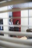 Collègues d'affaires souriant dans le bureau Photographie stock