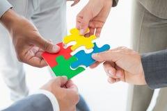 Collègues d'affaires tenant le morceau de puzzle photo libre de droits
