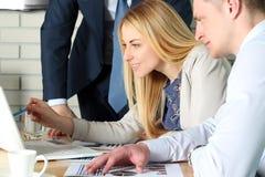 Collègues d'affaires travaillant ensemble et analysant les chiffres financiers sur un ordinateur portable Photo stock