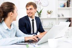 Collègues d'homme et de femme travaillant sur des ordinateurs Images stock