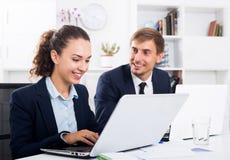 Collègues d'homme et de femme travaillant sur des ordinateurs Photo stock
