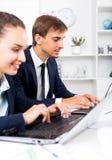 Collègues d'homme et de femme travaillant sur des ordinateurs Image stock