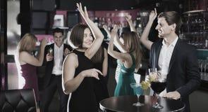 Collègues dansant sur la partie d'entreprise avec des cocktails dans des mains Image libre de droits