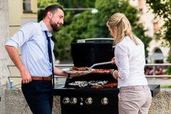 Collègues de bureau grillant des saucisses au BBQ après travail Photo stock
