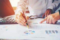 Collègues de l'équipe deux d'affaires discutant le graphique financier de nouveau plan Image libre de droits