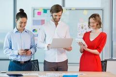Collègues de sourire d'affaires à l'aide du téléphone portable, du comprimé numérique et de l'ordinateur portable Images stock