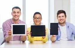 Collègues de sourire montrant à PC de comprimé l'écran vide Photographie stock libre de droits
