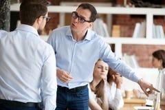 Collègues fâchés d'hommes d'affaires se disputant dans le bureau partagé images stock