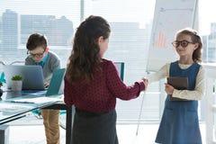 Collègues féminins donnant la poignée de main tandis qu'homme d'affaires utilisant l'ordinateur portable images stock