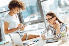 Collègues féminins positifs travaillant ensemble dans le bureau Photographie stock