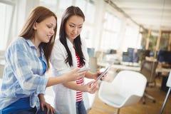 Collègues féminins tenant le comprimé numérique et le téléphone portable dans le bureau photos libres de droits