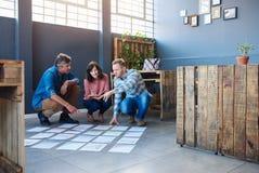 Collègues focalisés faisant un brainstorm avec des papiers sur un plancher moderne de bureau photographie stock